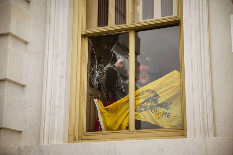 A member of a pro-Trump mob shatters a window with his fist from inside the Capitol Building after breaking into it on January 6, 2021 in Washington, DC.