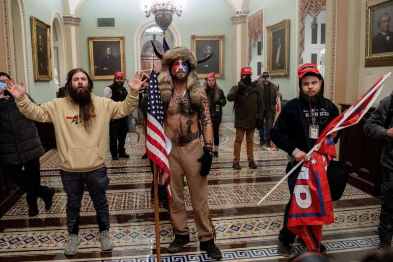 Supporters of US President Donald Trump, including Jake Angeli (C), a QAnon supporter known for his painted face and horned hat, enter the US Capitol on January 6, 2021, in Washington, DC.