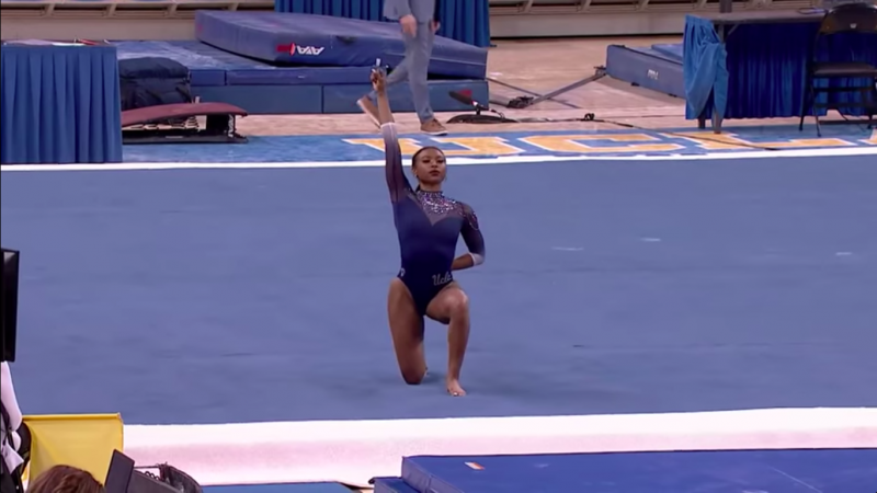 UCLA gymnast Nia Dennis proudly holds her fist aloft at the start of her now-viral 'Black Excellence' floor routine.