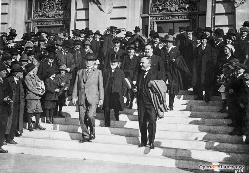 A smiling Mayor James Rolph on the steps of San Francisco's City Hall, with his coat slung over his arm. This image was taken in 1918, four years after the public opium burning.