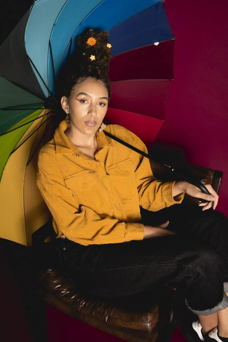Jada Imani wears a mustard yellow jacket and poses holding a multicolored umbrella.