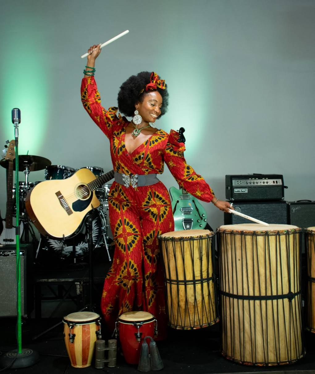 Queen Iminah plays the drums while wearing a guitar over her shoulder.