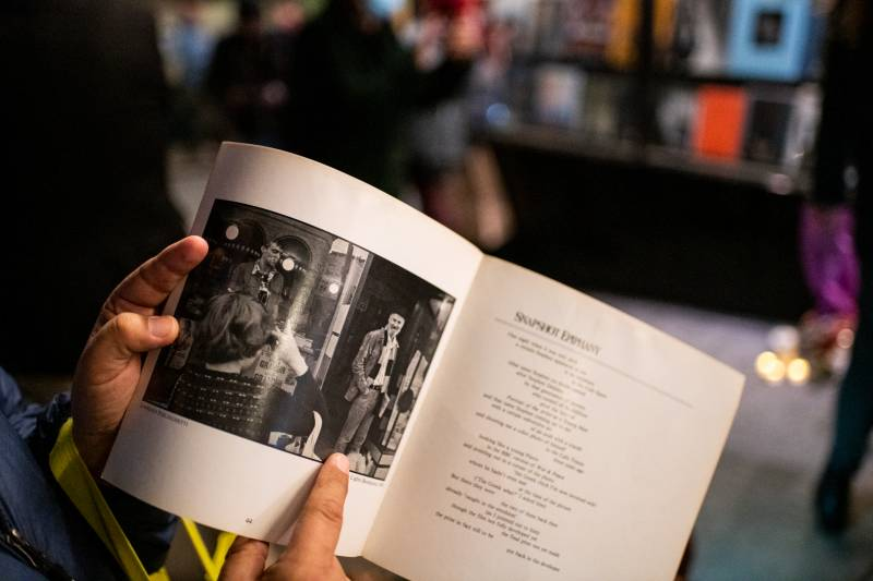 An attendee at the memorial points to a photo of Ferlinghetti in a poetry book outside of City Lights Books on Feb. 23, 2021.