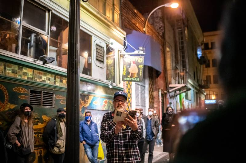Poet Charlie Getter reads from Lawrence Ferlinghetti's book Coney Island of the Mind during a vigil outside of City Lights Books on Feb. 23, 2021.