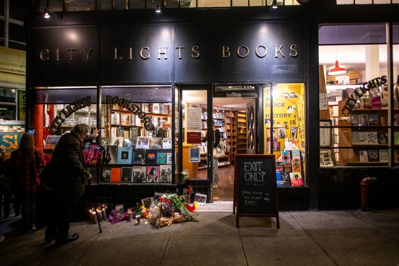 Flowers, candles and photos of Lawrence Ferlinghetti are left outside of City Lights Books on Feb. 23, 2021.