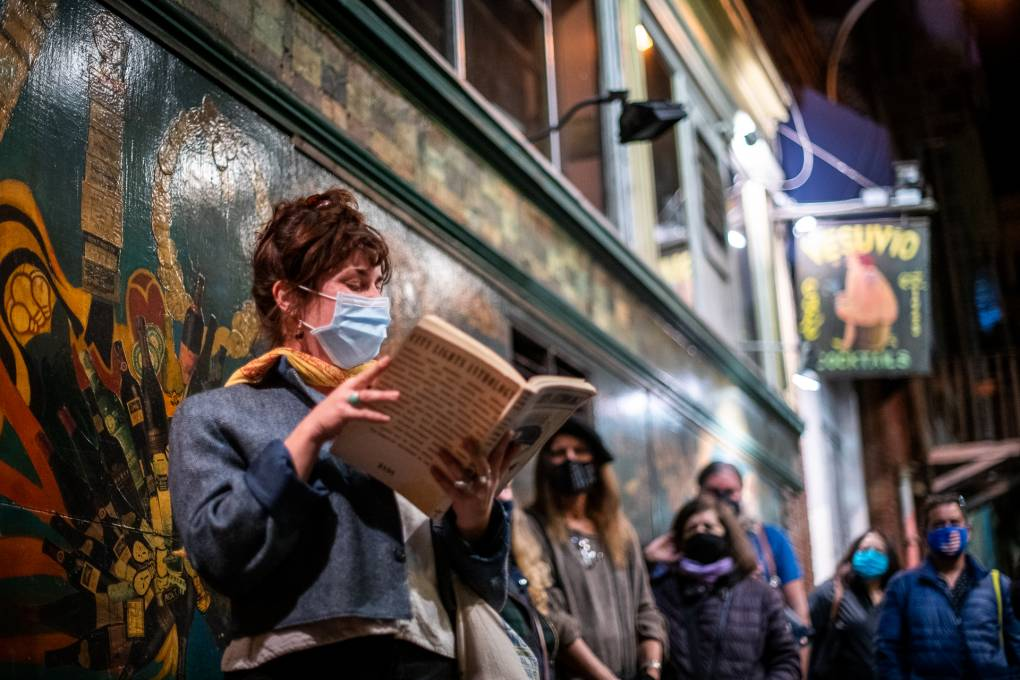 Hannah Forrester reads from a 1974 City Lights Anthology during a vigil for Lawrence Ferlinghetti outside of City Lights Books on Feb. 23, 2021.