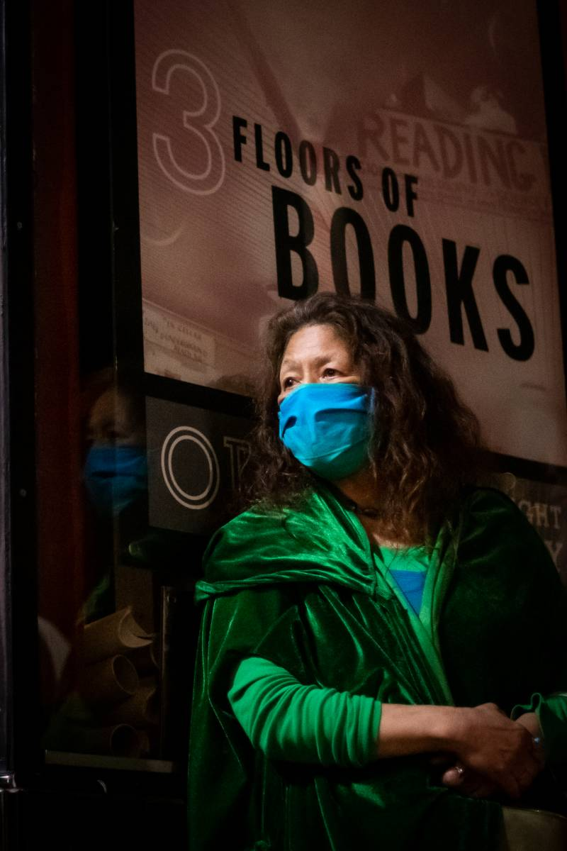 Leilani Chun listens to speakers during a vigil for Lawrence Ferlinghetti outside of City Lights Books on Feb. 23, 2021.