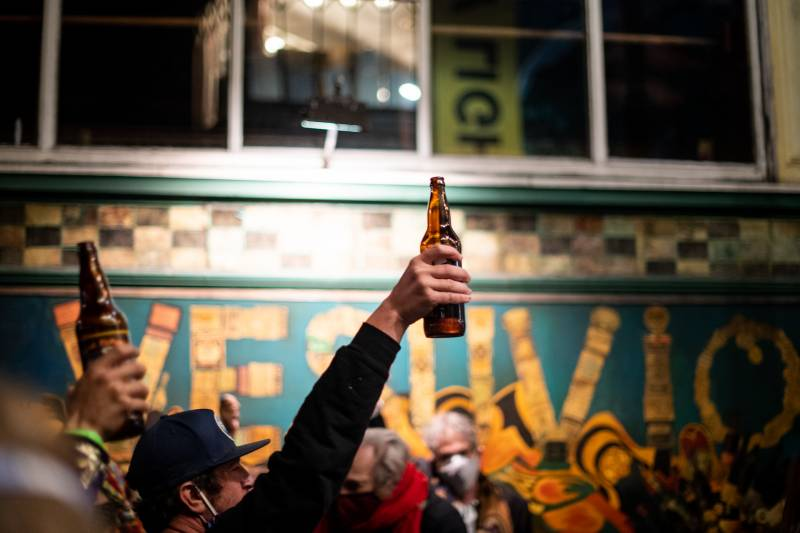 Bottles of beer are raised in the air during a cheers for Lawrence Ferlinghetti outside of City Lights Books on Feb. 23, 2021.