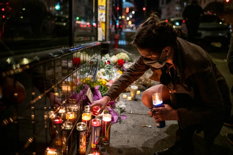 A woman lights a candle at a memorial for Lawrence Ferlinghetti outside of City Lights Books on Feb. 23, 2021.