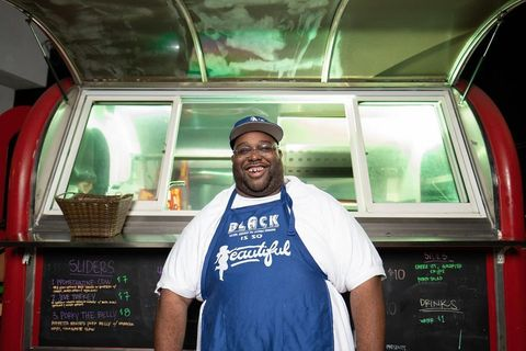 Champ Green stands in front of a food truck wearing a baseball cap and an apron.
