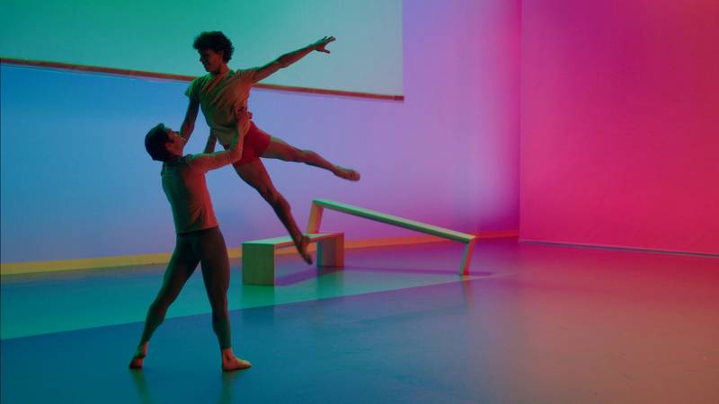 One male dancer holds another male dancer aloft in a teal and purple-tinged space.