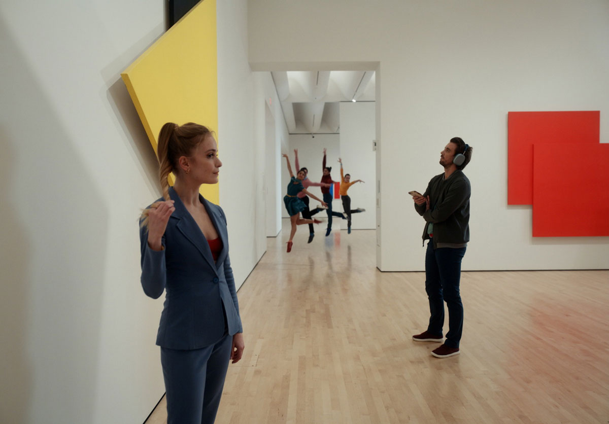 A woman twists her ponytail near a man who regards a painting while listening to an audio tour. Four dancers leap in unison down the hall from them.