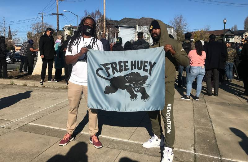 Two men hold a 'Free Huey' banner at the newly christened Huey P. Newton Way in West Oakland, Feb. 17, 2021.