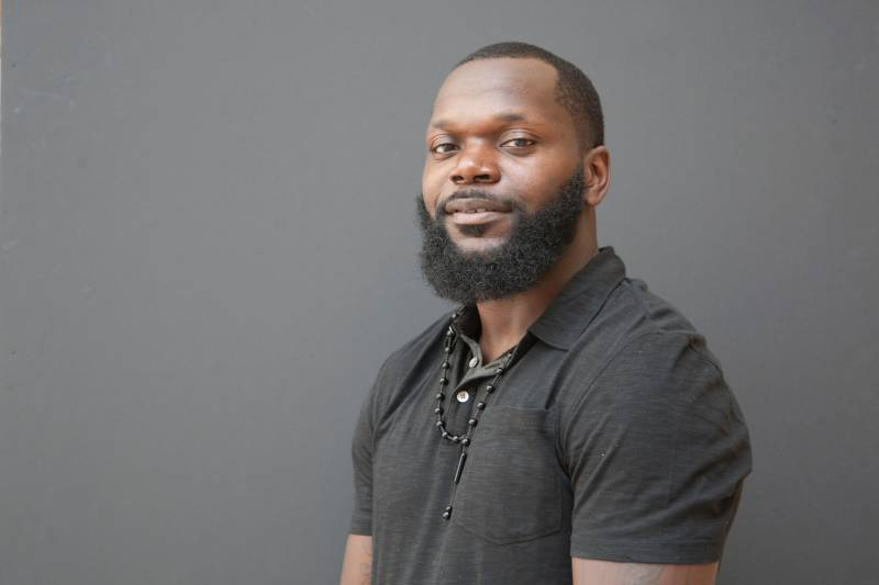 Antoine Johnson sits in front of a gray background wearing a dark gray polo T-shirt. His face is turned towards us with a slight smile and relaxed eyes. We can't see below his elbows but his arms seel to rest at his sides. His beard is neat and his hair looks freshly cut.