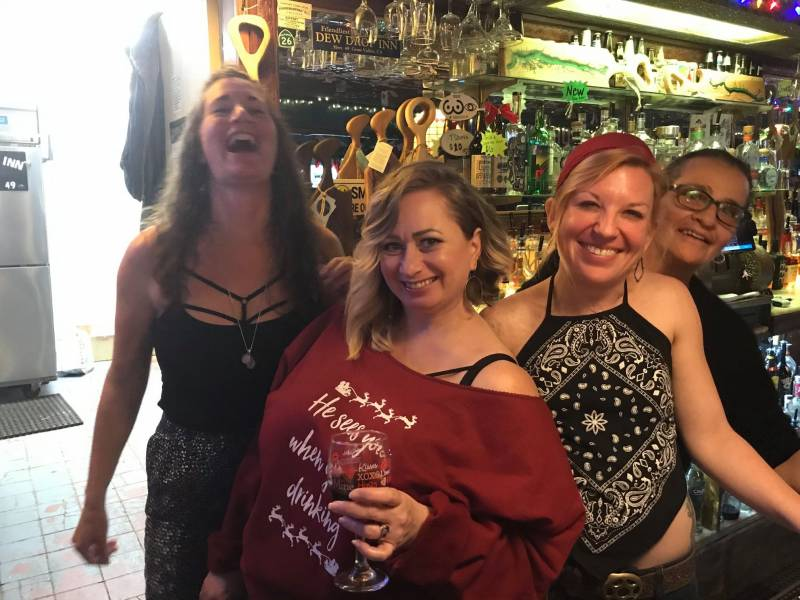 Behind the Dew Drop's bar, bartenders Kalli Scogna, owner Lori Holcomb Godfrey, Lori Savageau, and Vanessa.