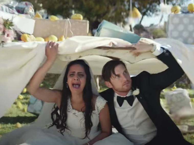 """A bride and groom hide under a table in Bud Light's """"Lemons"""" Super Bowl Ad."""