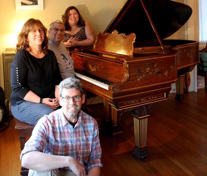 A family of two parents and two adult children pose around their grand piano in a cozy living room.