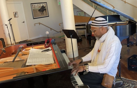 A man in a white sweater, jewelry and knit hat plays the piano.