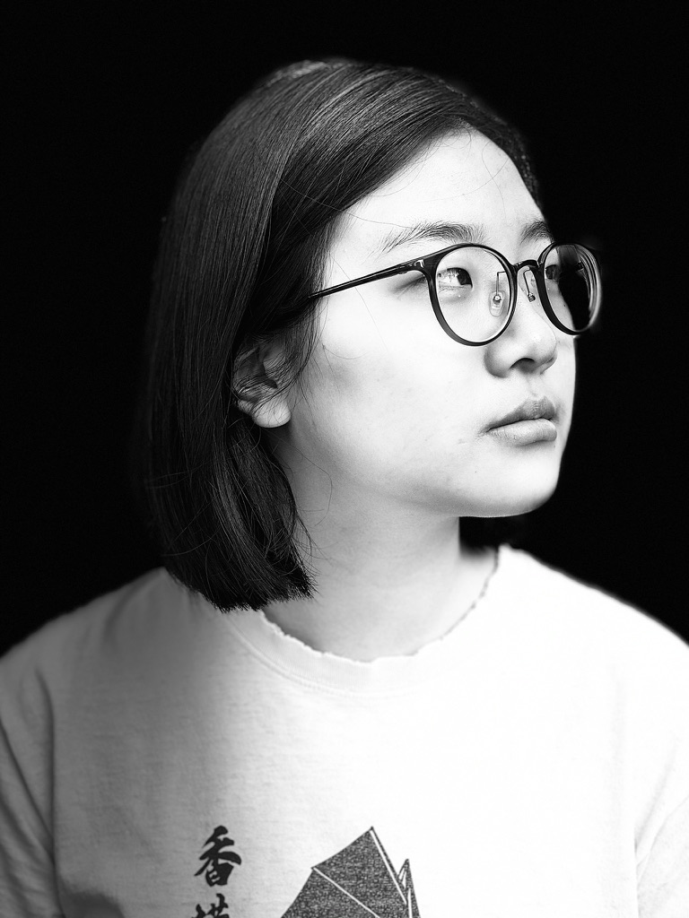 A young Asian American woman with glasses gazes into the distance in a back and white portrait.