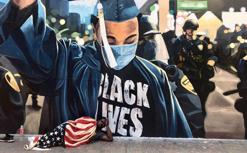 A man named Jeremiah sleeps wrapped in an American flag on the streets of downtown Oakland, beneath a large Black Lives Matter mural.