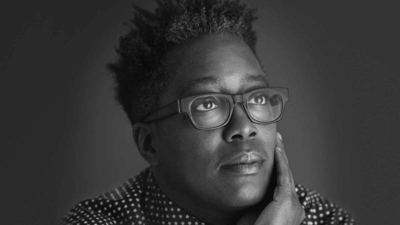 A black and white headshot of Cheryl Dunye. Her hair is cut short, she wears glasses and a collared shirt, one hand cups her face.