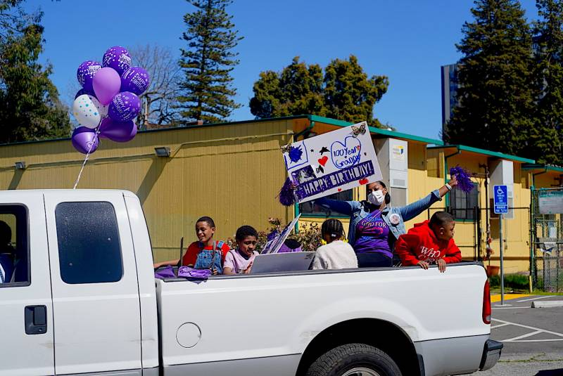 A pickup truck full of family members drives in the parade to celebrate Marcella Hubbard's 100th birthday.