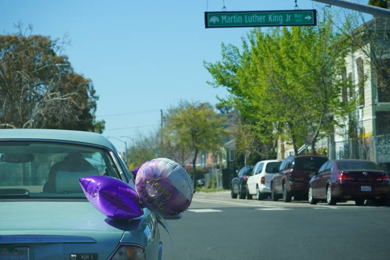 A car celebrating Marcella Hubbard's 100th birthday crosses Martin Luther King Jr. Way in Oakland.