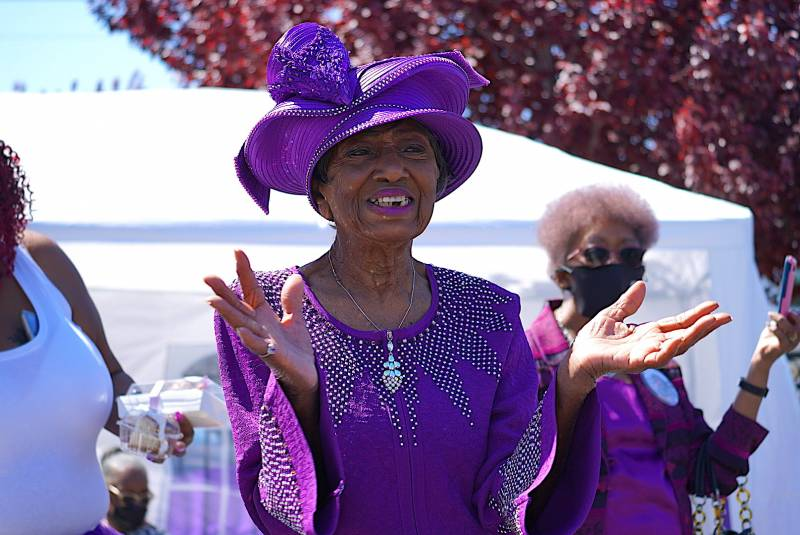 Marcella Hubbard smiles as she stands and cheers as people drive by in celebration of her 100th birthday.
