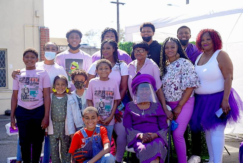 Mrs. Hubbard sits in the center as family members gather around her for a photograph. Almost everyone is wearing purple.