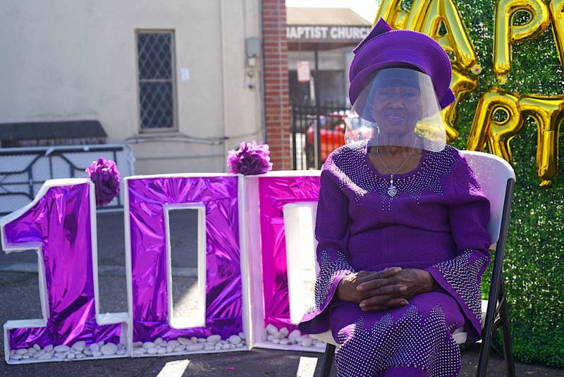 "Marcella Hubbard, wearing all purple and a COVID-19 safe protective face shield, sits in front of a huge ""100"" sign as she celebrates her 100th birthday."