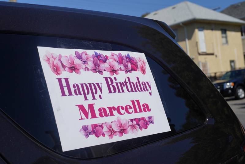 "A ""Happy Birthday Marcella"" sign mounted in the window of an automobile."