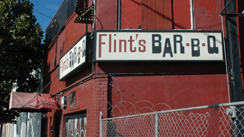 """The exterior of Flint's Barbecue, with the """"Flint's Bar-B-Q"""" sign visible"""