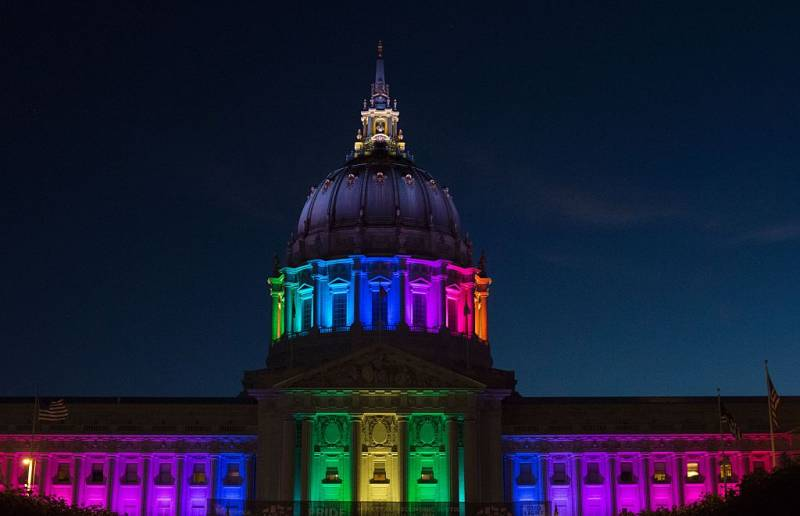 San Francisco City Hall is lit up with rainbow colors.