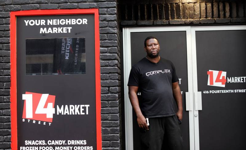A man poses outside of a grocery store that's in the process of being built out.