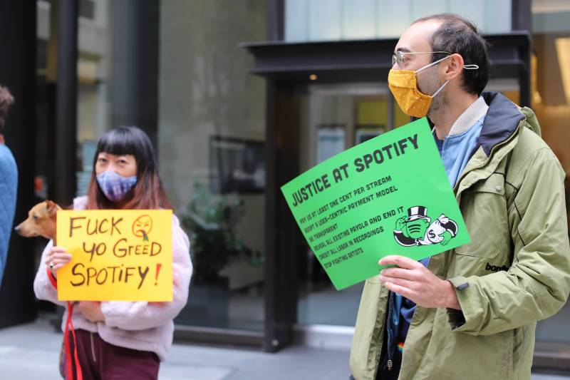 """A protester holds a sign that says """"Fuck yo greed Spotify!"""" Another holds one that reads """"Justice at Spotify."""""""