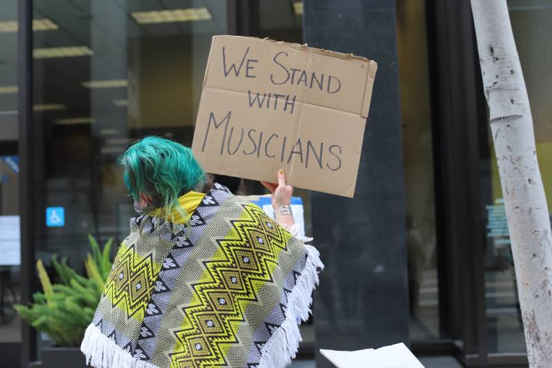 """A woman with green hair holds a sign that says """"We stand with musicians."""""""
