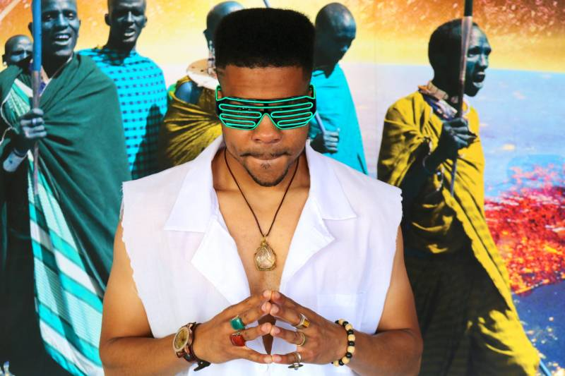 Theo Hollingsworth in character as Sirius Lee, standing with his fingers clasped in front of his chest, while wearing futuristic sunglasses.