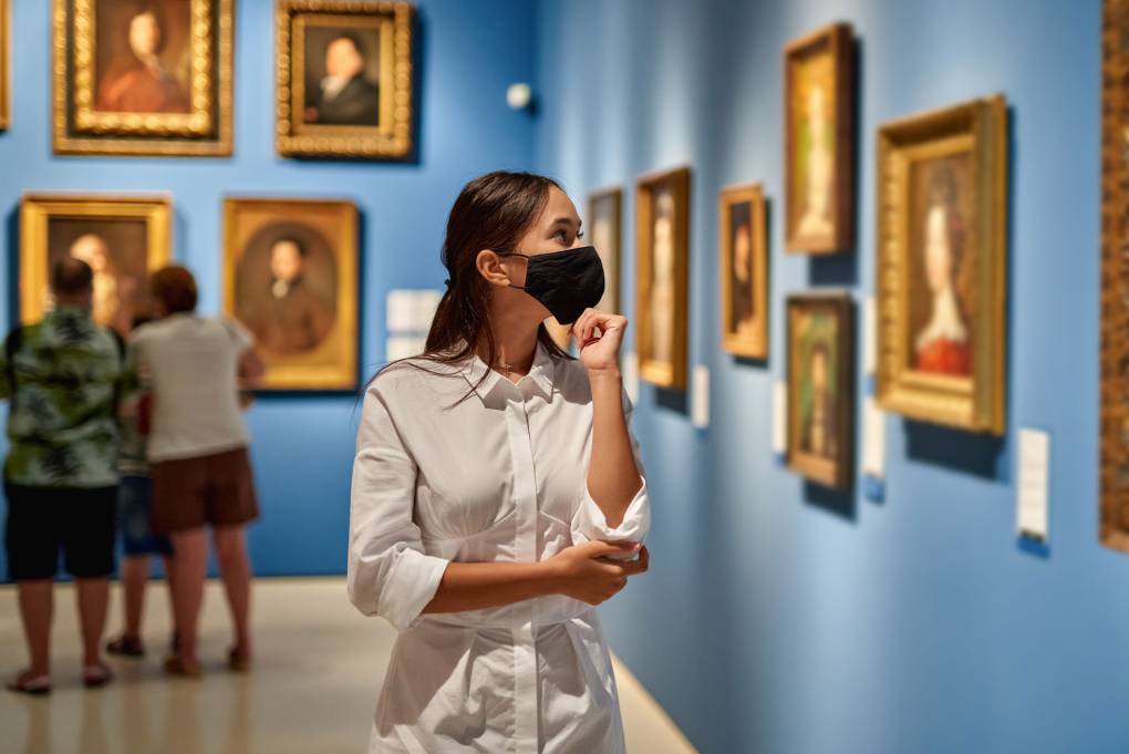 A woman in a mask looks at art in a museum