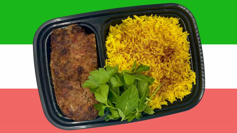 """A takeout container with Persian kabob digi (aka """"Persian meatloaf""""), turmeric, and fresh herbs."""