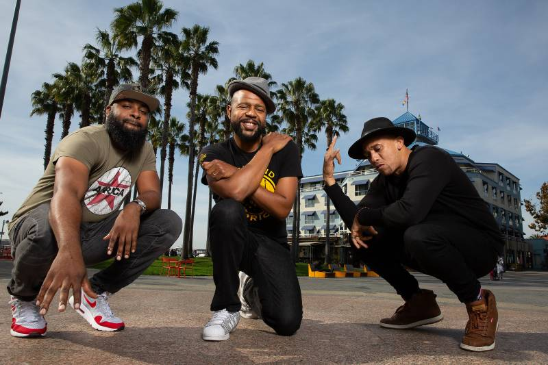 Three musicians smile and pose in front of palm trees.