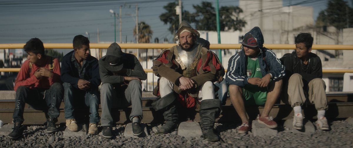 A man dressed as a conquistador sits on a railway track with other men.