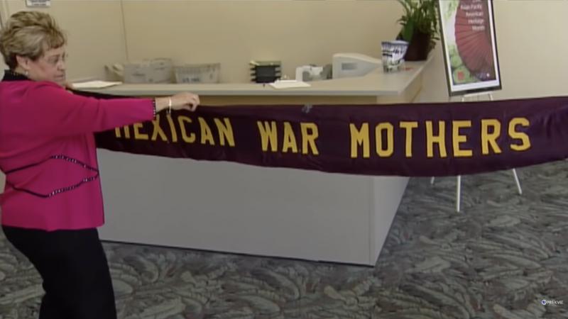 Enriqueta Andazola's granddaughter Diana Salgado Zuñiga unfurls a vintage 'Mexican War Mothers' banner, during KVIE documentary, 'Valentia: Mexican-Americans in World War II.'