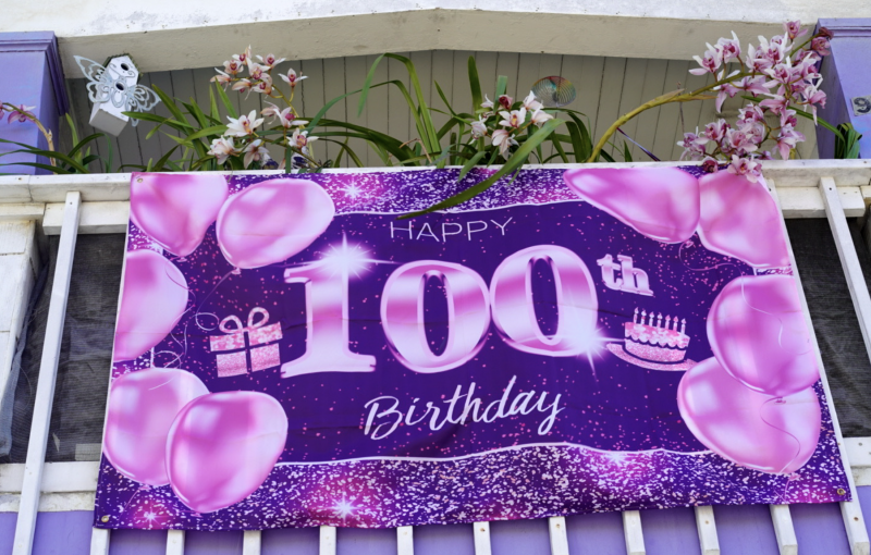 "A purple ""Happy 100th Birthday"" banner mounted on the front of Mrs. Hubbard's house"
