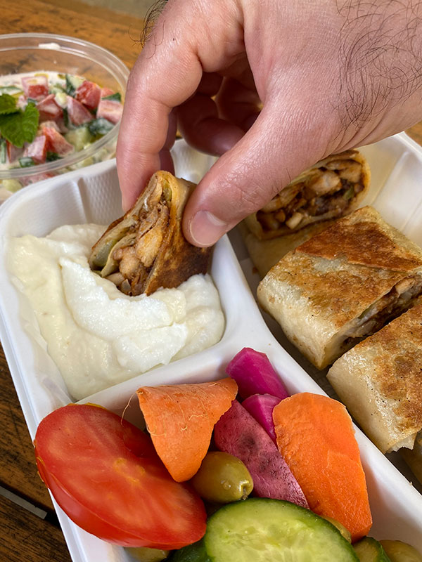 A hand dipping a sliced shawarma wrap into white garlic sauce.