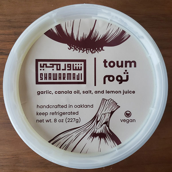 A tub of toum from Shawarmaji; the label lists the ingredients: garlic, canola oil, salt, lemon juice