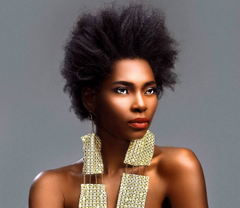 A woman with bare shoulders, Afro hair and large earrings gazes into the distance.