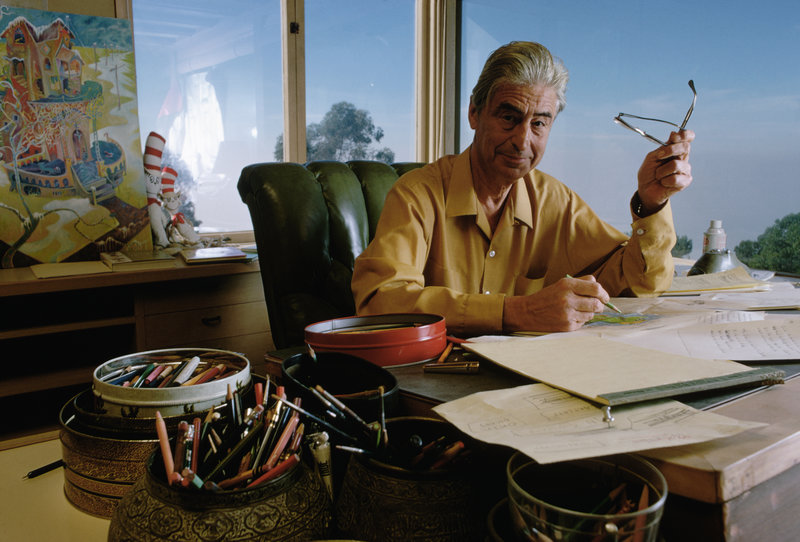 Dr. Seuss drawing at his desk.