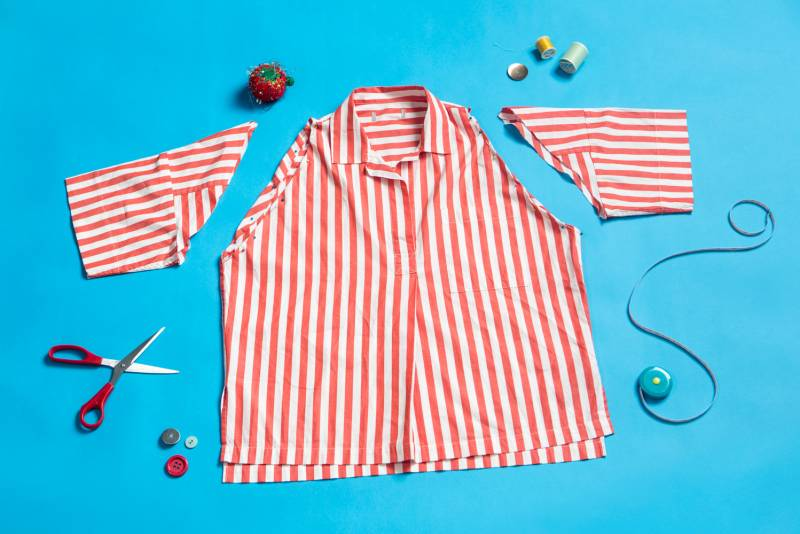 A shirt laid out with the sleeves cut off. Symphony Clarke, known as the Thrift Guru on social media, says one way to give clothes a fresh feel is by revamping them—cutting them up or adding some new details.