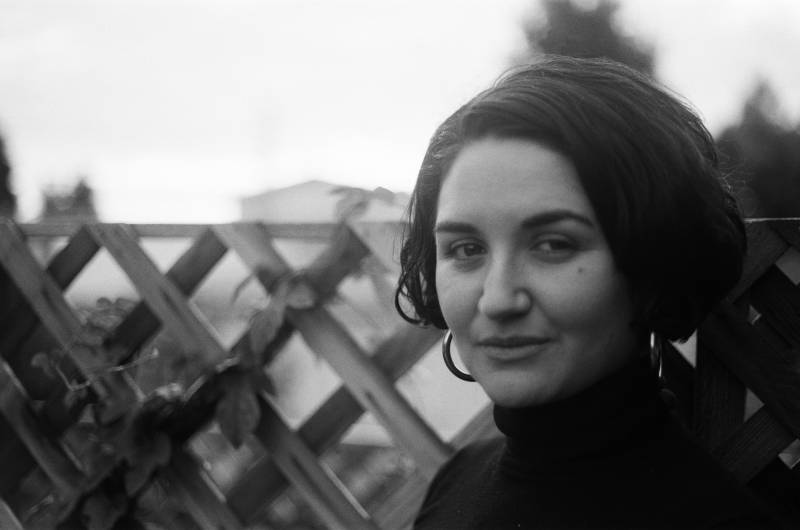 A black and white headshot of Maya Cueva. She gives us a half smile, is wearing hoop earings and her curly hair is in a bob. She wears a black turtleneck in front of a fence.