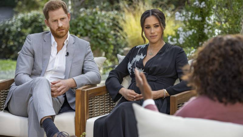 Prince Harry and Meghan Markle sit in a garden opposite their interviewer, Oprah.